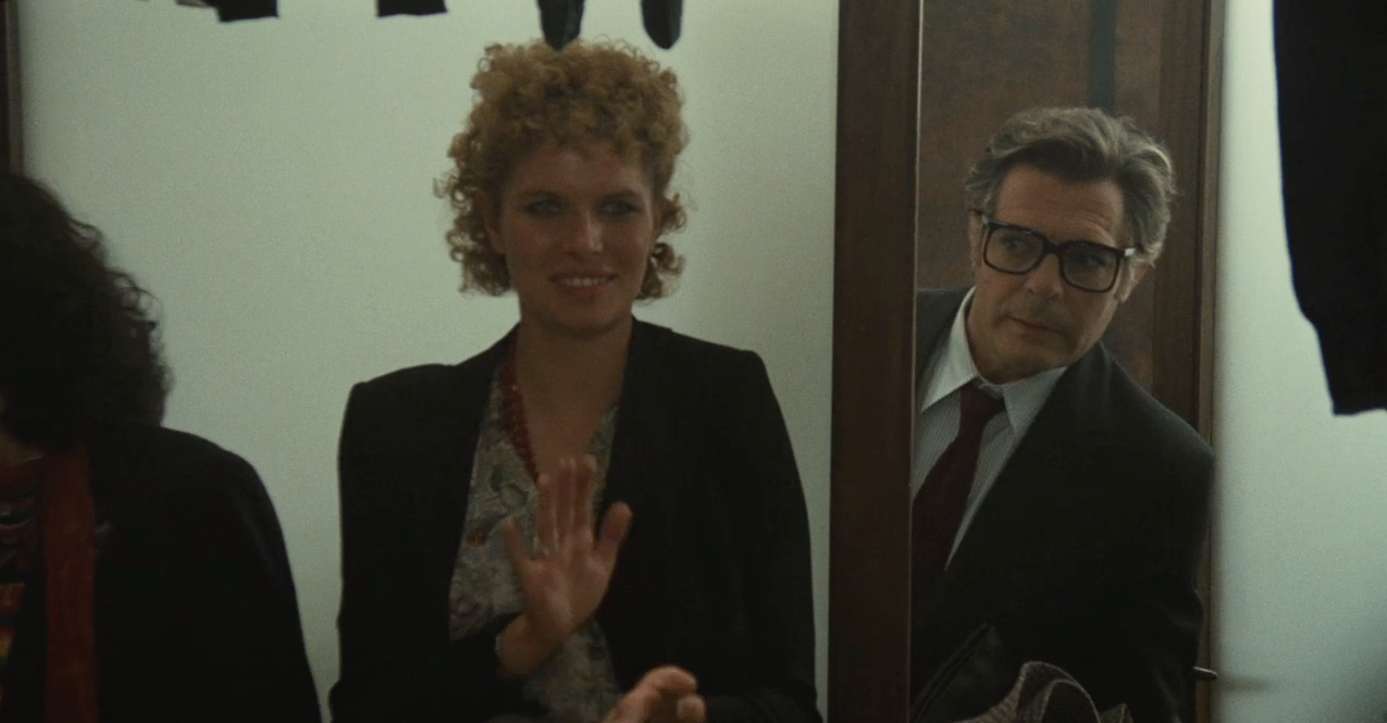 Marcello Mastroianni in City of Women (1980). Snaporaz, still in his suit and tie, is peering out from behind a slightly open door. He is staring at a young blonde woman standing in front of the door, she is looking away and applauding.