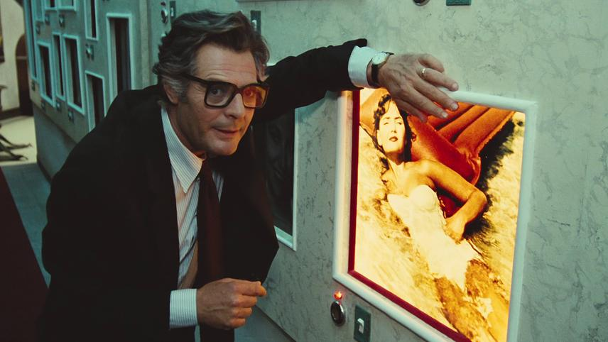 Marcello Mastroianni in City of Women (1980). Snaporaz, a greying middle-aged Italian man, is wearing large glasses and a black suit with a red tie. He is leaning against a poster of an attractive woman in a white swimsuit, lounging in a shallow pool.